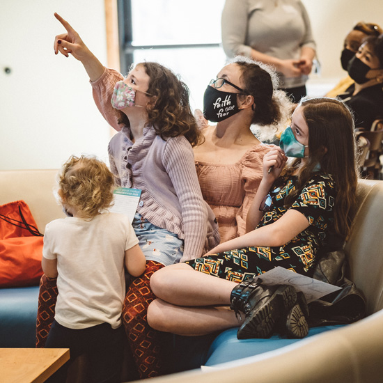 Young mother watching church on a television with her daughters