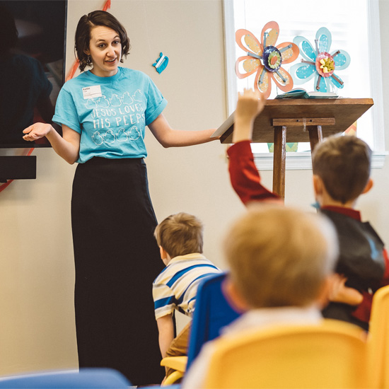 Lady in a blue shirt teaching a lesson about Jesus to 5 year olds