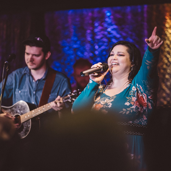 Female worship leader in flower dress singing in a Christian church conference with a man playing guitar