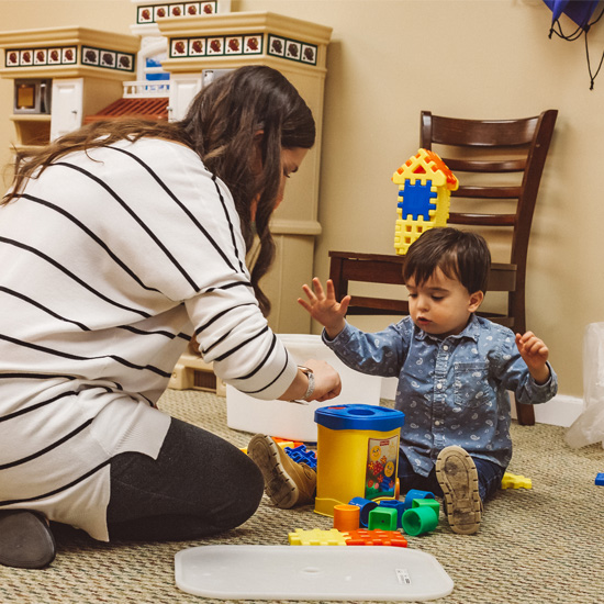 2 year old boy playing with blocks and with his kids ministry teacher on the floor