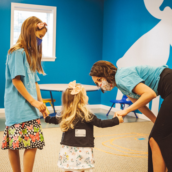 4 year old girl with bow in her hair being welcomed into her kids ministry room by her teacher