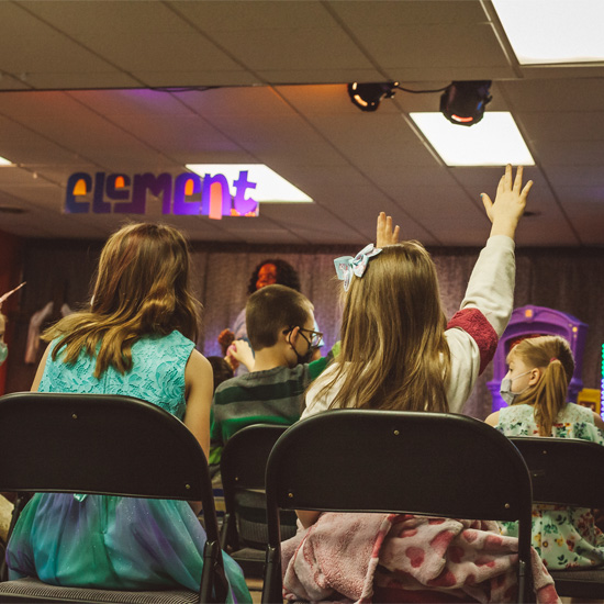 Fifth grade girls raising their hands during a christian kids ministry service