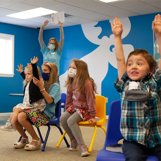 Young boys and girls raising their hands during worship in their kids christian ministry room