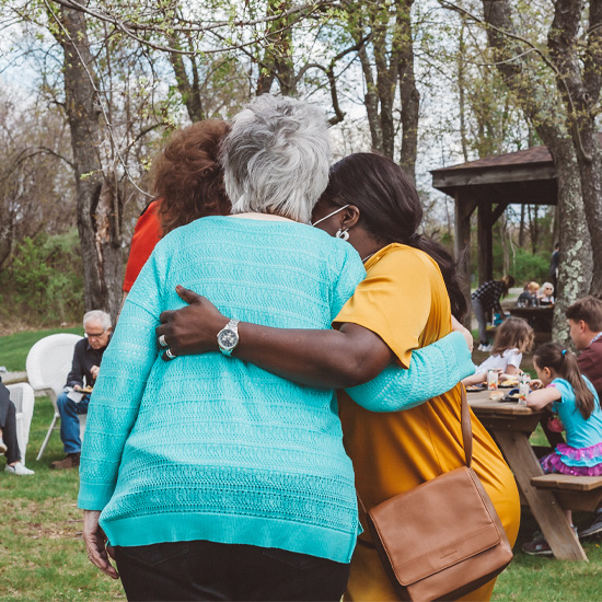 Three ladies at an outdoor church community event welcoming and hugging each other