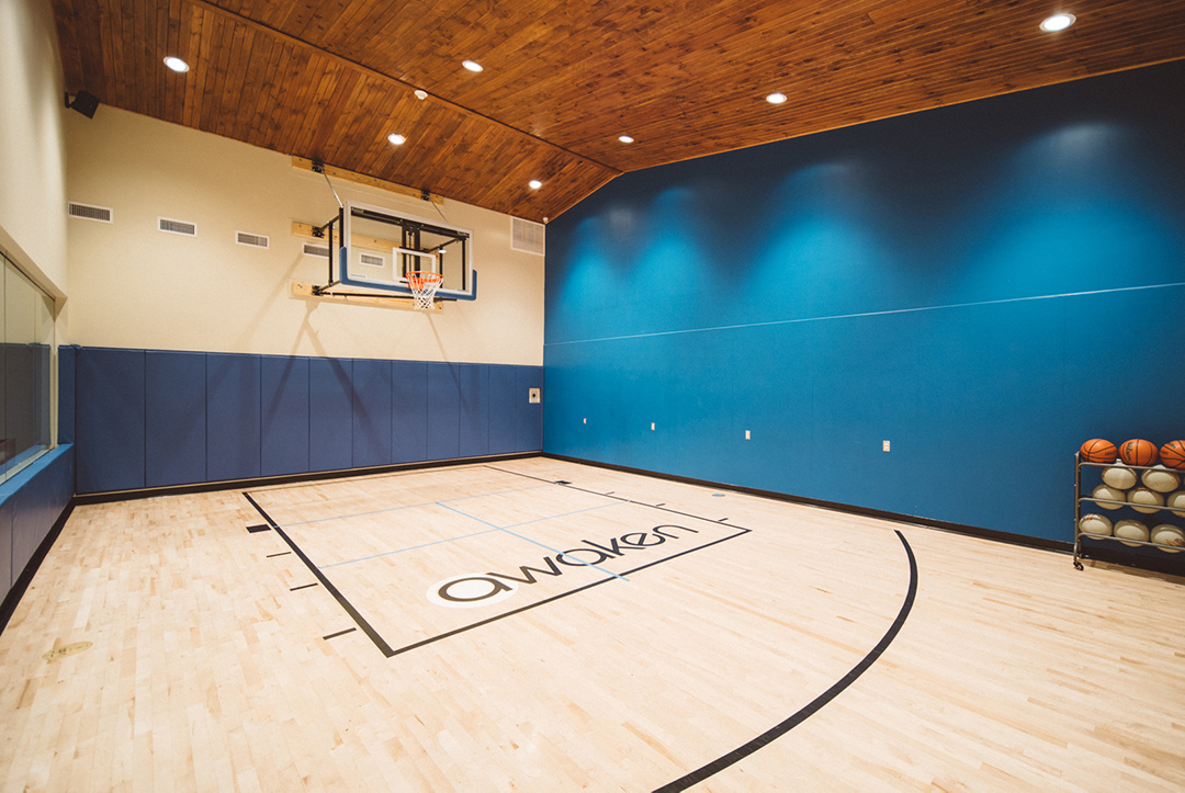 Large indoor basketball half court with glass wall and backboard and a blue wall