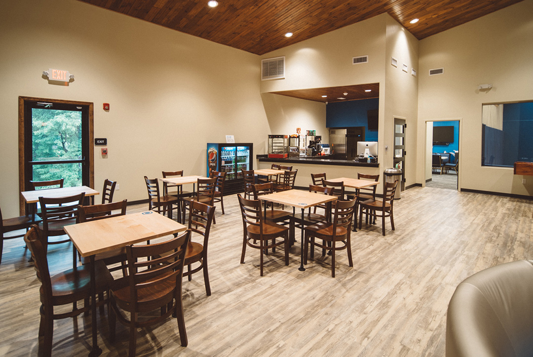 Youth center cafe with tables and chairs and stocked with soft drinks, coffee, and snacks