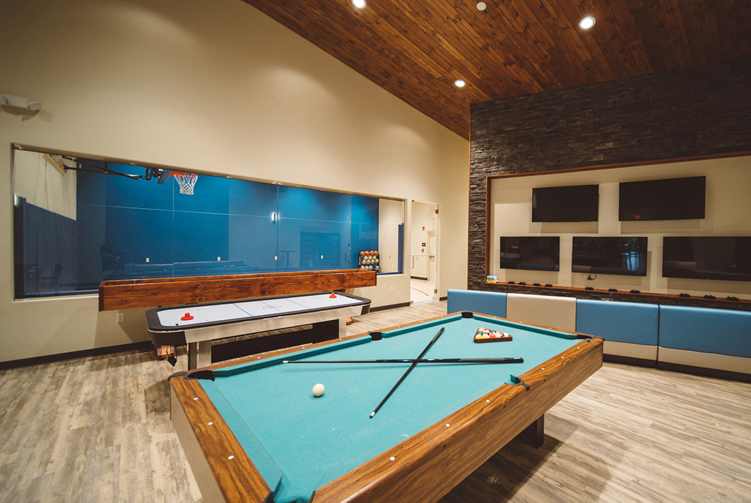 Green felt pool table, air hockey table, shuffle board, video game wall, and half-court basketball court