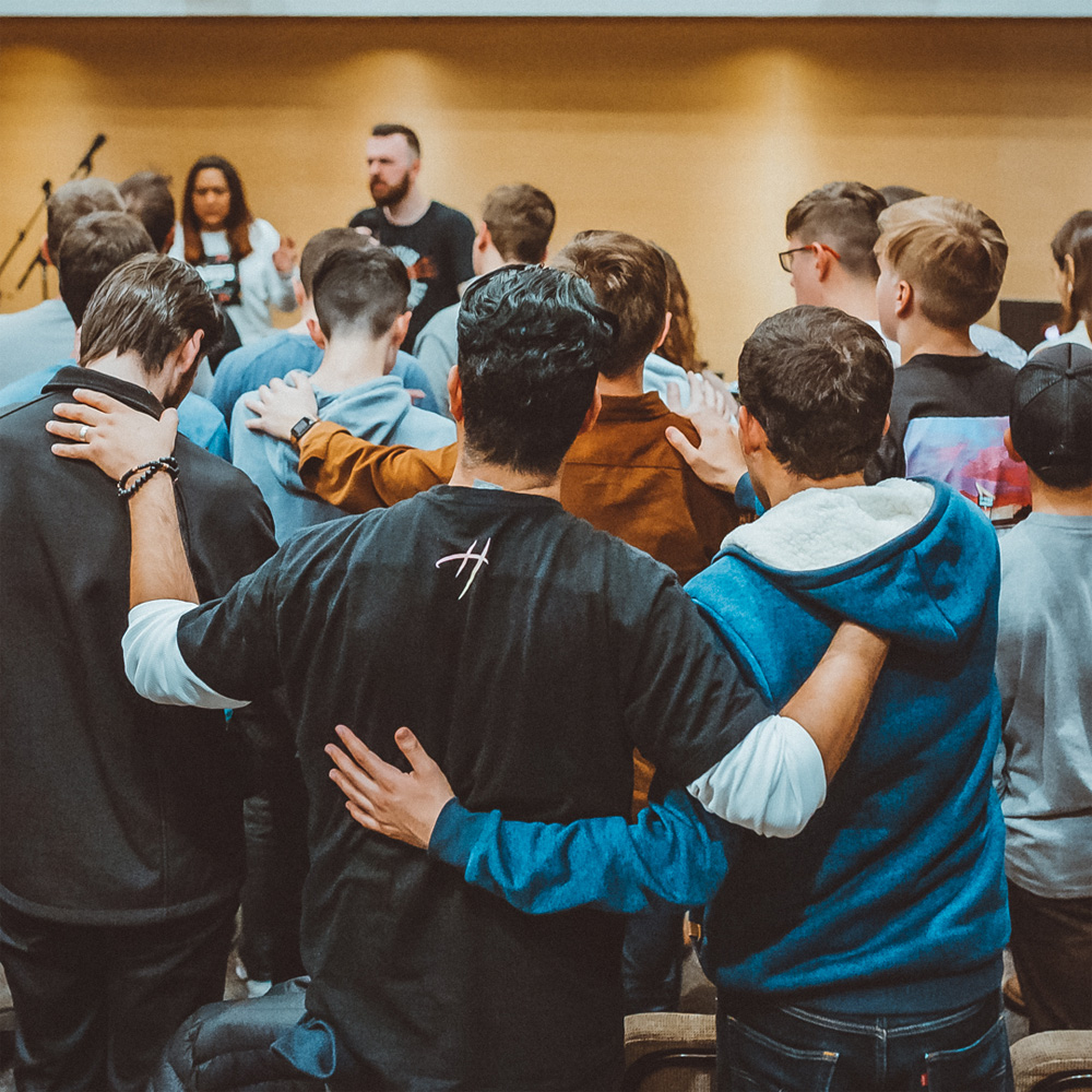 Group of men and women praying together and over one another during a Kingdom Advancers event