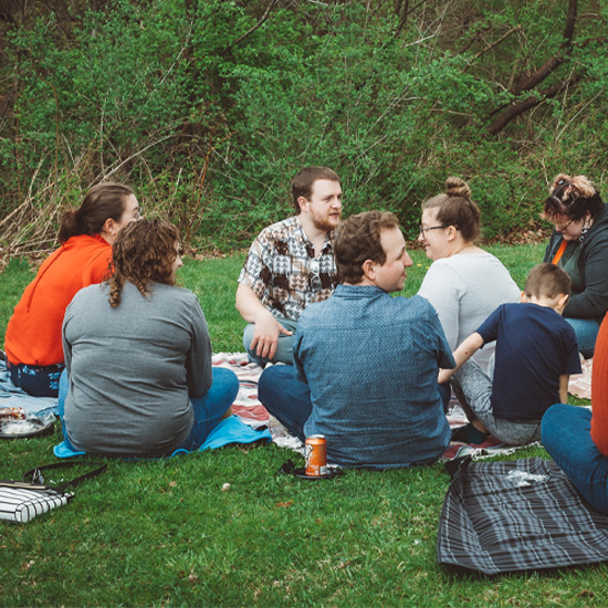 A West Ridge Church Life Group composed of men and women meeting outside in a park during the spring